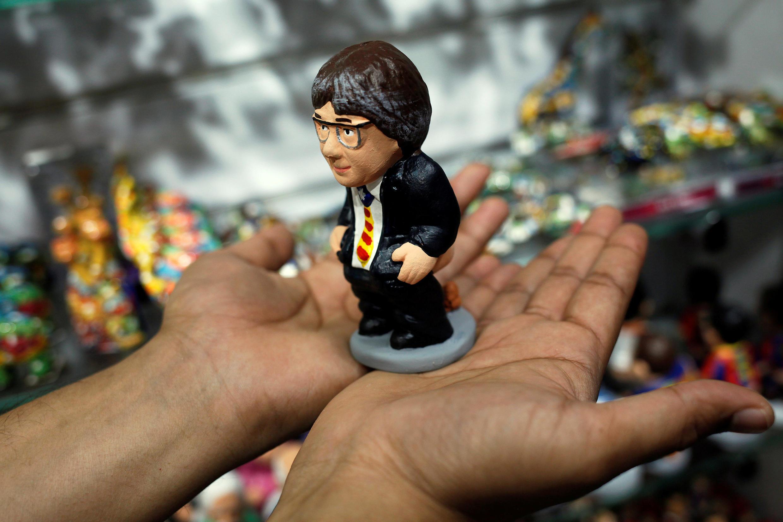 """Un vendedor muestra una figurita del Carles Puigdemont, representando al famoso santón catalán """"caganer"""". Barcelona, 30 de octubre de 2017."""