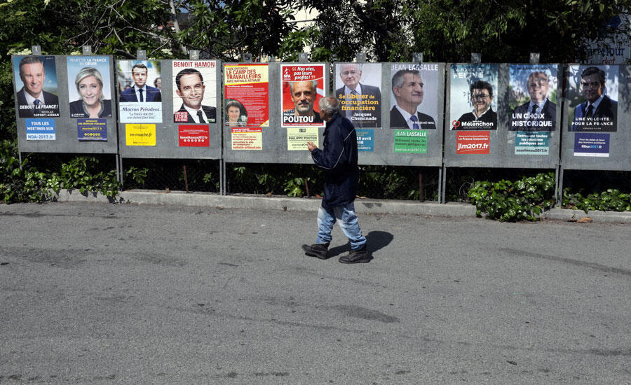 Un homme marche devant les affiches des 11 candidats en lice pour l'élection présidentielle de 2017 en France, à Saint André de la Roche, près de Nice, le 10 avril 2017.