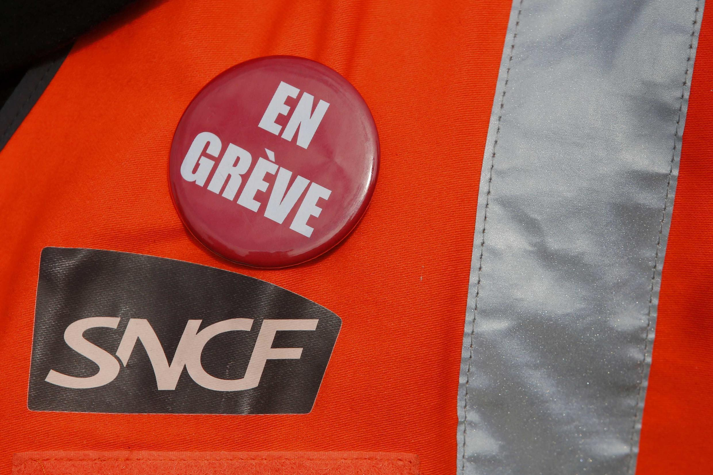 """A railworker with a badge saying """"On strike"""""""