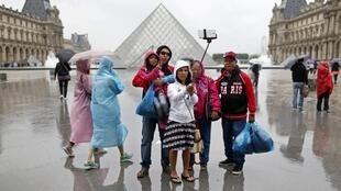 "Turistas se toman un fotografía con palos para selfie, ""selfie sticks"", frente al Louvre."