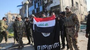 Le drapeau irakien prend la place de celui du groupe EI, à Ramadi, le 28 décembre 2015.