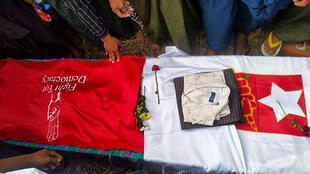 Mourners stand around the coffin of Khet Thi, who along with other poets in Myanmar dared to speak out against February's military coup