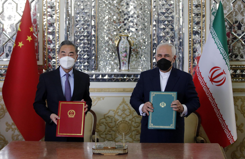 Los ministros Wang Yi (izq) y Mohammad Javad Zarif posan con sendas copias del acuerdo de cooperación el 27 de marzo de 2021 en Teherán