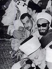 Nasser et Ahmad bin Yahya du Yémen du Nord regardent l'objectif, durant la conférence de Bandung en avril 1955. Le prince Fayçal d'Arabie saoudite est à l'arrière-plan, et Mohammed Amin al-Husseini au premier-plan.