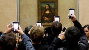 "FILE PHOTO: Visitors take pictures of the painting ""Mona Lisa"" (La Joconde) by Leonardo Da Vinci at the Louvre museum in Paris, France, December 3, 2018. Picture taken December 3, 2018."