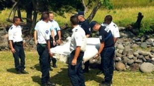 Polícias franceses  carregam destroço do avião numa praia da ilha da Reunião.Julho 2015
