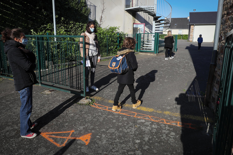 Na escola de ensino fundamental de Chasne sur Illet, os adultos franceses usam máscara para receber as crianças. Marcas no chão lembram as medidas de distância social