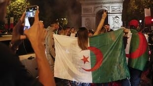 Algeria supporters team celebrate on the Champs-Elysees Avenue in Paris on 14 July 2019 after their team's win over Nigeria in the Africa Cup of Nations football tournament.