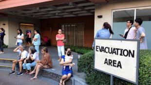 Vecinos evacuados de un edificio luego del sismo en la ciudad de Makati.