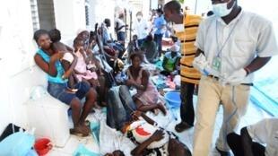 Des victimes du choléra et leur famille attendent à l'établissement médical de Saint-Marc, le 20 octobre 2010.