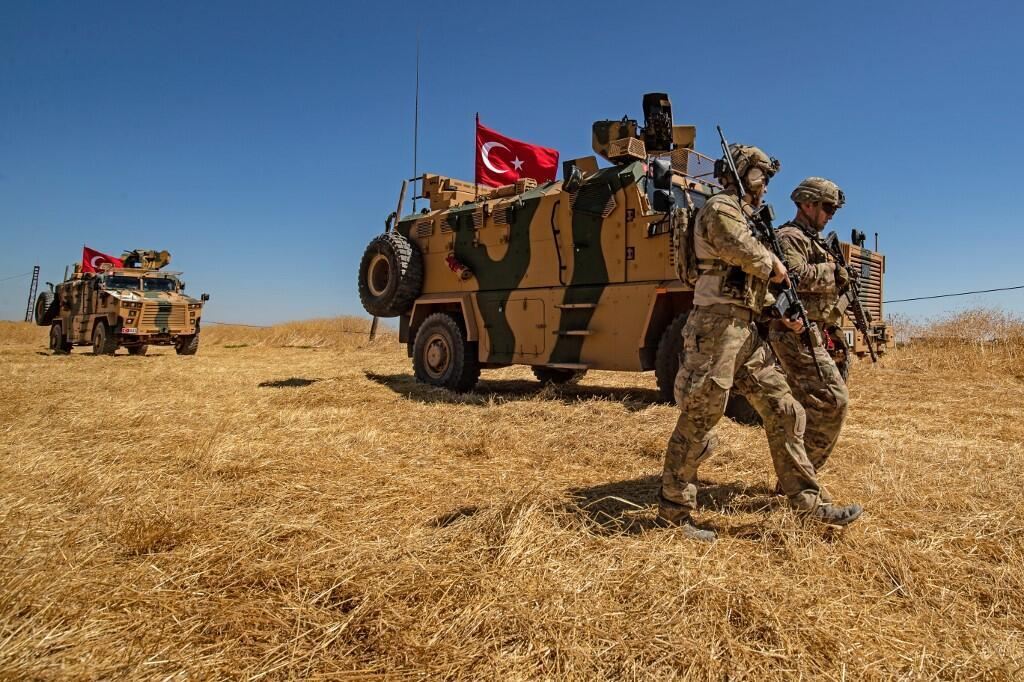 US troops walk past a Turkish military vehicle during a joint patrol with Turkish troops near the Syrian town of Tal Abyad on the Turkey-Syria border, 8 September 2019.