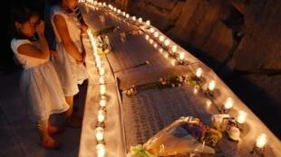 Crianças rezam em frente ao memorial destinado às vítimas do crash do avião da Japan Airlines (JAL) no vilarejo de Ueno, em 12 de agosto de 2015.