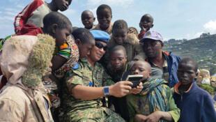 Sake, Nord-Kivu, RD Congo: Un soldat de maintien de la paix montrant une courte vidéo de bande dessinée à un groupe d'enfants au marché de Karuba, le 7 septembre 2015.