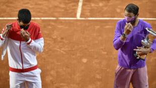 El español Rafael Nadal (Der.) sosteniendo el trofeo de campeón junto al serbio Novak Djokovic (izquierda),  cons su distinción, , ajustan su máscara protectora mientras posan después de la final del Abierto de Italia en el Foro Itálico, el 16 de mayo de 2021 en Roma, Italia.