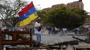 Un manifestant de l'opposition devant une barricade, le 20 février à Caracas.