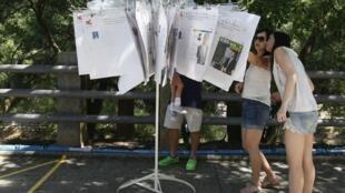 Devant un bureau de vote, les électeurs s'informent sur les candidats. Hong Kong, le 9 septembre 2012.