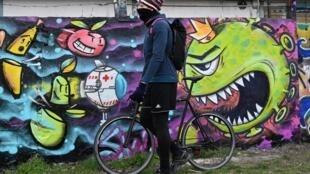 Un cycliste passe devant un mur de graffitis près du lieu où se déroule chaque année Sziget Island Festival à Budapest, annulé à cause du coronavirus, le 25 mars 2020.