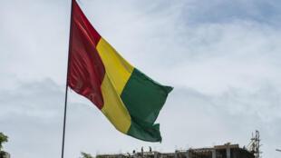 Le drapeau de la Guinée flotte dans le ciel de Conakry.