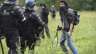 A protester faces French riot gendarmes, during a second eviction of environmental protesters from the area in Notre-Dame-des-Landes.