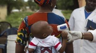 Un personnel de santé contrôle la température d'un bébé à la frontière entre la Guinée et le Mali, le 2 octobre 2014.