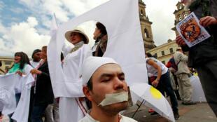 Dans la rue à Bogota, les Colombiens manifestent en faveur de l'accord de paix signé le 24 novembre avec les FARC ou contre comme cet homme baillonné.