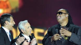 «Laissez-moi regarder ça !», a plaisanté le chanteur, aveugle depuis l'enfance, en enlevant ses lunettes noires pour faire mine d'admirer le trophée. A gauche, l'animateur télé Nagui et Charles Aznavour.