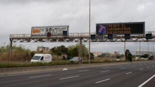 Sur une autoroute près de Barcelone, le 16 mars 2020, un panneau affiche le message: «Arrêtons le coronavirus. Restons à la maison.»