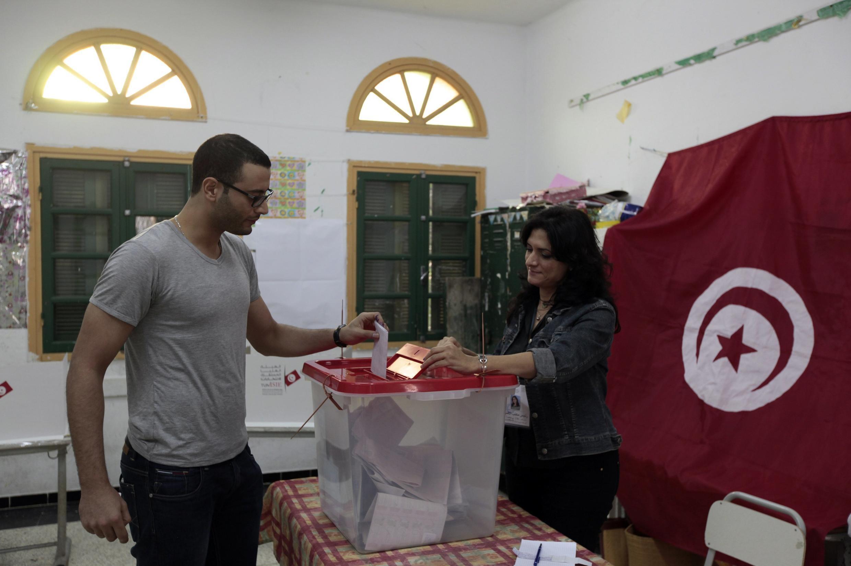 Eleitor deposita voto em urna de Sousse, na Tunísia.