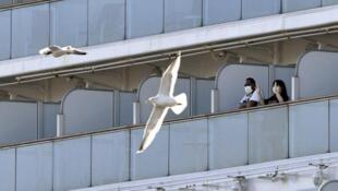 存档图片:被困在钻石公主号豪华大邮轮上的乘客 Image d'archive: Les passagers portent des masques sur le bateau de croisière Diamond Princess au terminal de croisière de la jetée de Daikoku, à Yokohama.