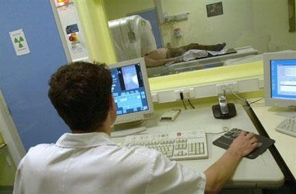Une infirmière surveille l'administration de rayons sur la tumeur d'un patient atteint d'un cancer.
