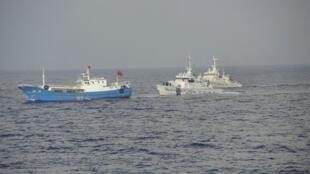 Le bateau chinois (G) poursuivi par le bateau des gardes-côtes japonais (D) au large de Miyako, le 2 février 2013.