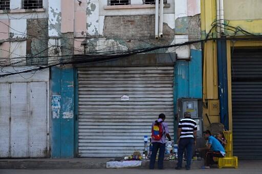 Ambulantes venden productos en la vereda afuera de una tienda cerrada en Maracaibo, Estado de Zulia, Venezuela, durante un masivo corte de luz el 23 de Julio de 2019.