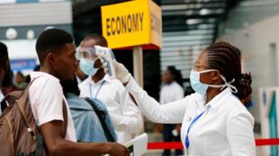 Uma agente de saúde verifica a temperatura de um passageiro como rotina de segurança contra o coronavírus no aeroporto internacional de Kotoka, em Gana.