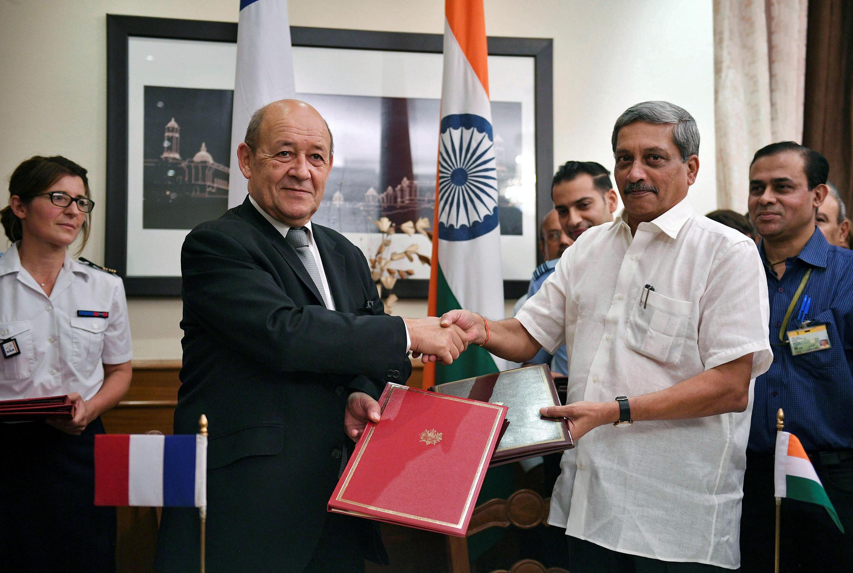Le ministre français de la Défense, Jean-Yves Le Drian (G) et son homologue indien Manohar Parrikar se serrent la main après après la signature des contrats de vente d'avions Rafale, à New Delhi, le 23 septembre 2016.