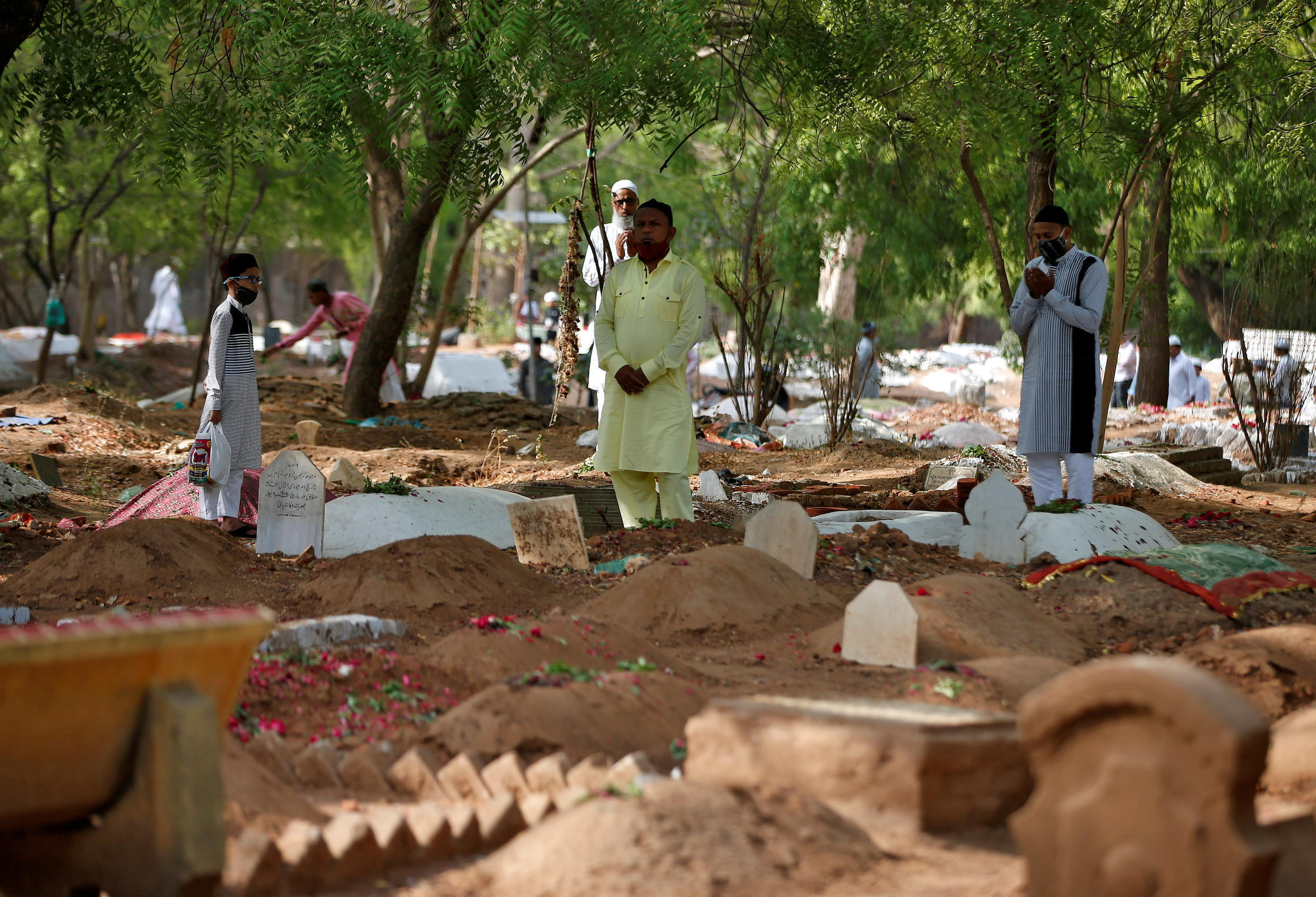 Muslims pray next to the graves of their relatives, including those who died from Covid-19, to mark Eid al-Fitr in Ahmedabad, India, 14 May, 2021