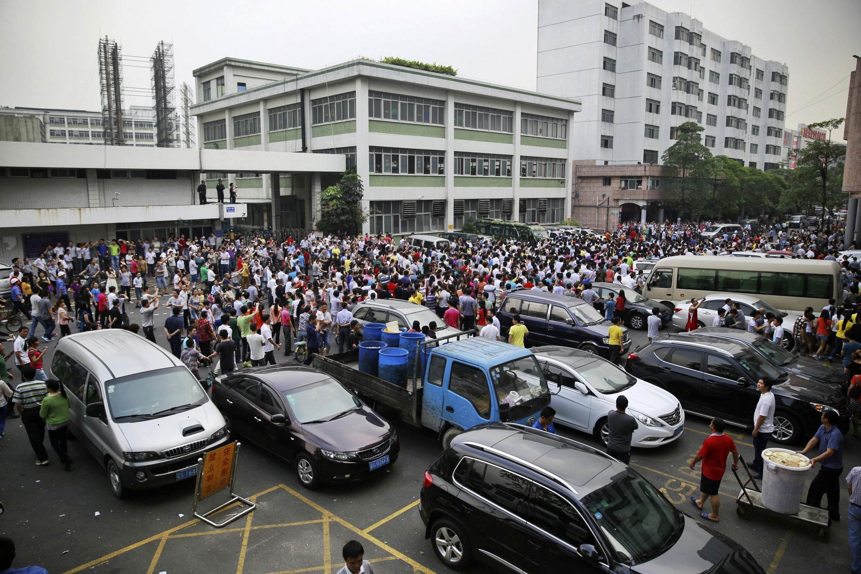 Công nhân biểu tình trước cổng công ty giày thể thao Dụ Nguyên, tại TP. Đông Quản, tỉnh Quảng Đông, Trung Quốc, ngày 18/04/2014. Cuộc bãi công lớn nhất trong thời gian ít năm gần đây.