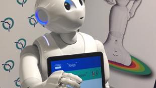 Робот Pepper общается с посетителями транспортного агентства. Париж, 13 декабря 2017 г.