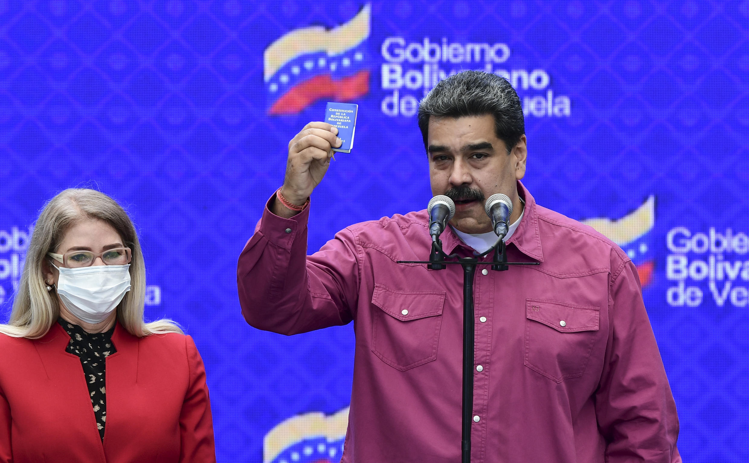 Venezuelan President Nicolas Maduro with his wife Cilia Flores gestures to photographers as he votes in legislative elections in Caracas, on December 6, 2020