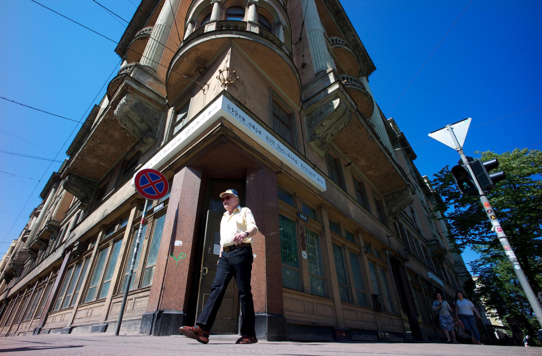 """Un homme passe devant le """"Stura maja"""" ou """"la Maison du coin"""", ancien siège social du KGB soviétique à Riga, Lettonie le 9 juillet 2014."""