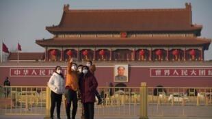 Du khách mang khẩu trang ngừa virus corona, chụp hình kỷ niệm trước Thiên An Môn, Bắc Kinh, Trung Quốc, ngày 30/01/2020.