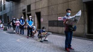 Varias personas guardan la distancia de seguridad mientras hacen cola para obtener gratuitamente una prueba de detección del coronavirus frente a una clínica gubernamental de Hong Kong, el 29 de julio de 2020 en el distrito de Sham Shui Po