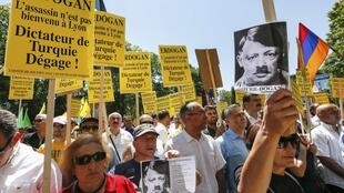 """Protesters bore placards declaring  """"Erdogan. The assasin is not welcome in Lyon. Turkey's Dictator - Get Out"""""""