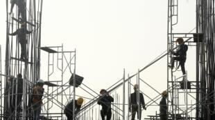 Công nhân làm việc trên một công trường xây dựng tại Hà Nội, ngày 18/12/2014.