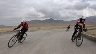 Massuma (G) et Zahra Alizada (D), les deux soeurs de l'équipe nationale afghane de cyclisme féminin lors d'un entraînement près de Kaboul.