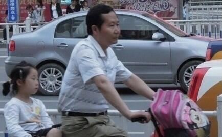 """六一儿童节后在中国网络""""疯传""""的一张安徽芜湖市副市长詹云超骑车送女儿上学的照片。"""