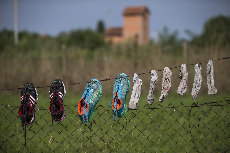Imigrantes colocam sapatos e meias para secar na cerca construída na fronteira entre a Sérvia e a Hungria.