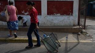 Une Vénézuélienne porte des bouteilles d'eau, remplies à partir d'une source de fortune ouverte dans une rue de Maracaibo, le 23 juillet 2019.
