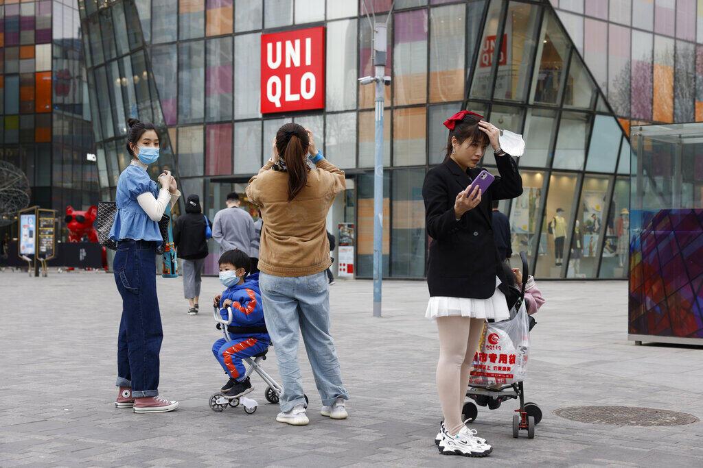 Foto de ilustración: Visitantes de un centro comercial con máscaras ante una tienda de Uniqlo en Pekín el lunes 29 de marzo de 2021.