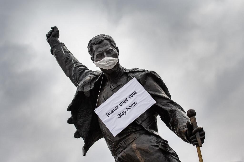 A photograph taken on March 23, 2020 in Montreux shows the statue of Queen's late singer Freddie Mercury wearing a protective facemask