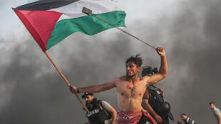 ابو عمرو، جوان مبارز فلسطینی، که در یک دست پرچم فلسطین و در دست دیگر فَلاخَن دارد. عکس از مصطفی هسونا، عکاس-خبرنگار خبرگزاری آناتولی ترکیه، دوشنبه ۲۲ اکتبر/٣۰ مهر، نوار غزه